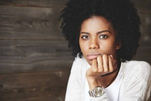 Close-up portrait of young black melancholic female looking at the camera with bored expression on her pretty face, having her chin on her hand, wearing watches, isolated on wooden background